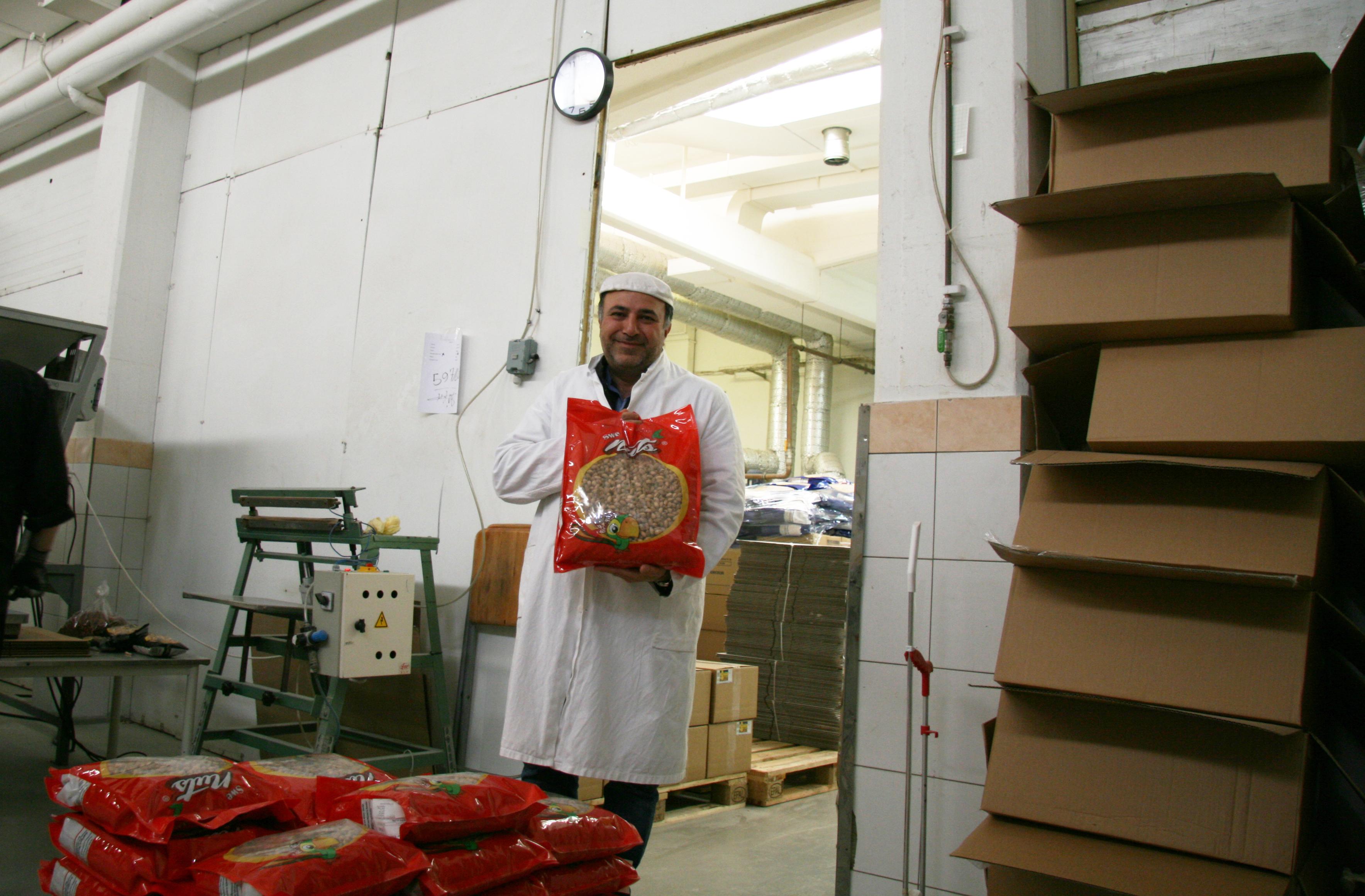 En nöjd rosteriägare med sin slutprodukt, rostade mandlar.